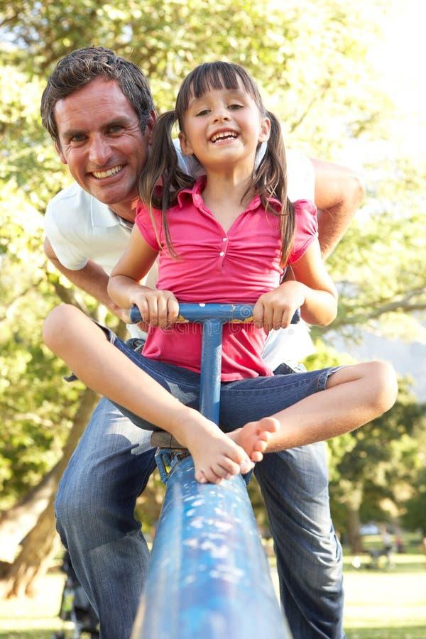 Vader en de Dochter die de berijden op zien Zaag stock fotografie