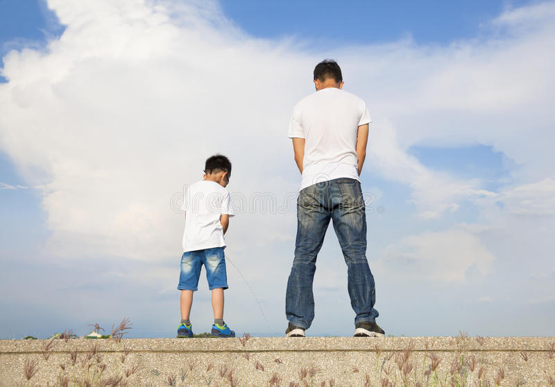 Vader en de zoon die zich op een steenplatform de bevinden en plassen samen stock fotografie