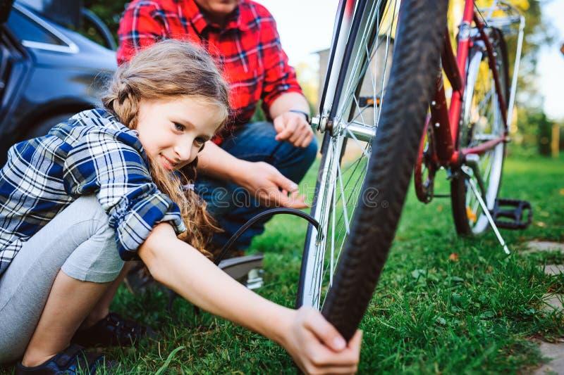 Vader en dochter bevestigende problemen met fiets openlucht in de zomer royalty-vrije stock afbeelding