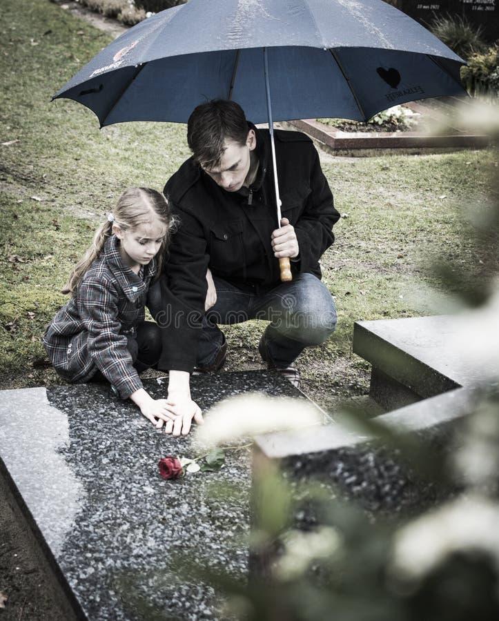 Vader en dochter bij graf royalty-vrije stock afbeeldingen
