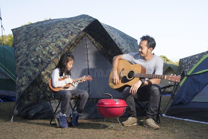 Vader en dochter bij het kamperen het spelen ukelele stock afbeeldingen