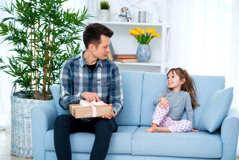 Vader en dochter of broer en zuster met een gift binnen de ruimte Het concept van de vaderdagvakantie, de Dag van Kinderen royalty-vrije stock fotografie