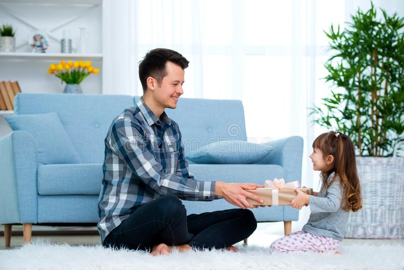 Vader en dochter of broer en zuster met een gift binnen de ruimte Het concept van de vaderdagvakantie, de Dag van Kinderen stock afbeelding