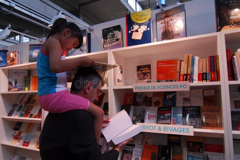 Vader en dochter de zitting op zijn schouders allebei las een boek stock afbeelding
