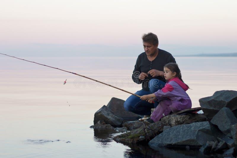 Vader en dochter die bij de zomerzonsondergang vissen op meer stock afbeeldingen