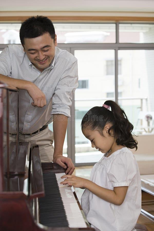 Vader en dochter die de piano spelen stock fotografie