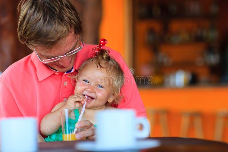 Vader en dochter die drank in koffie hebben stock afbeeldingen