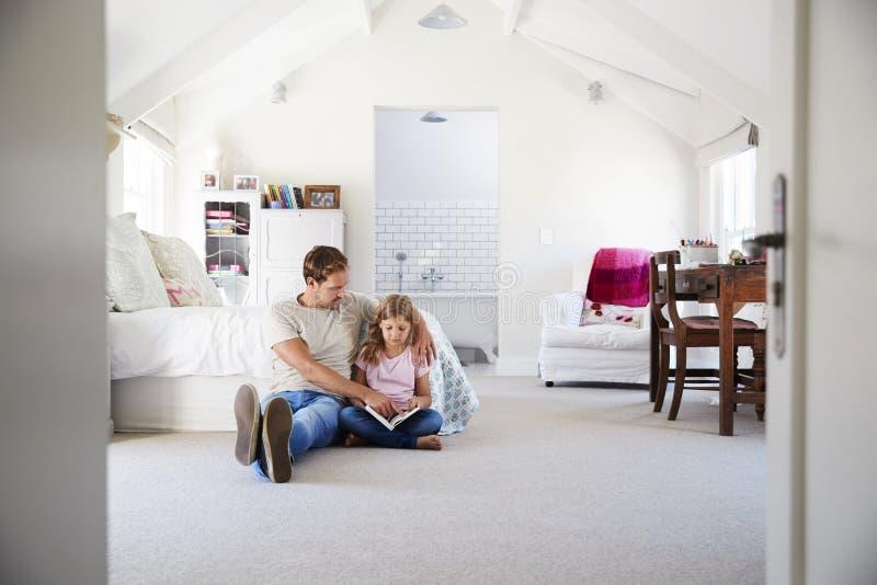 Vader en dochter die een boek samen in haar slaapkamer lezen royalty-vrije stock fotografie