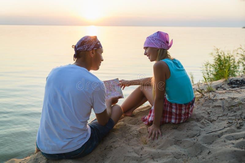 Vader en dochter die en kaart rusten bekijken Het concept van de reis en van het toerisme stock foto
