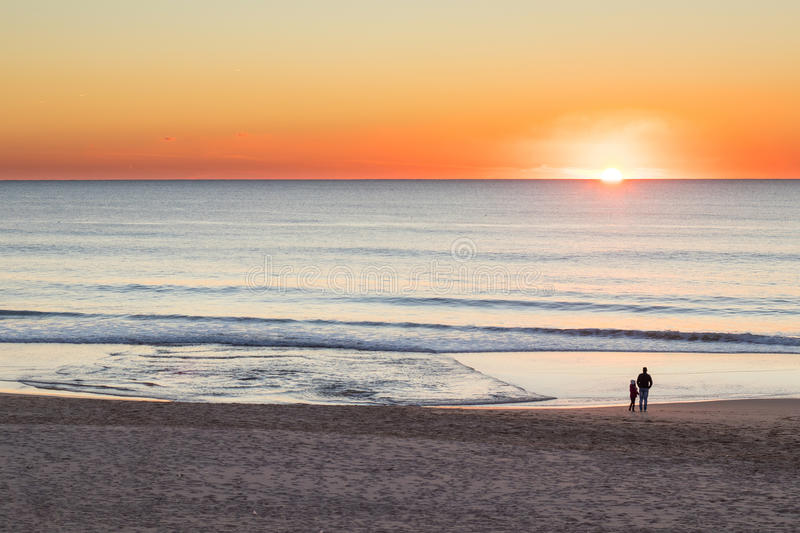 Vader en dochter die op de zonsondergang letten royalty-vrije stock afbeelding