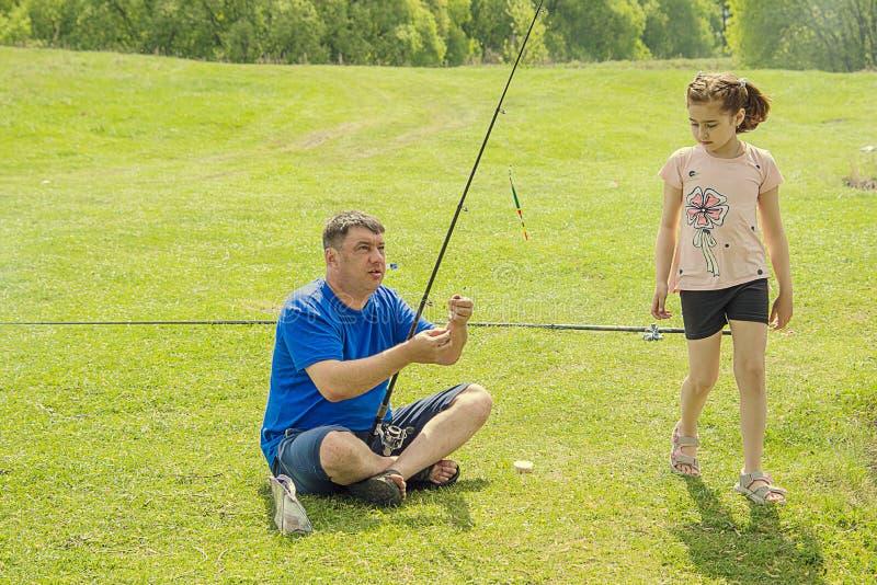 Vader en dochter die op een hengel vissen stock afbeeldingen