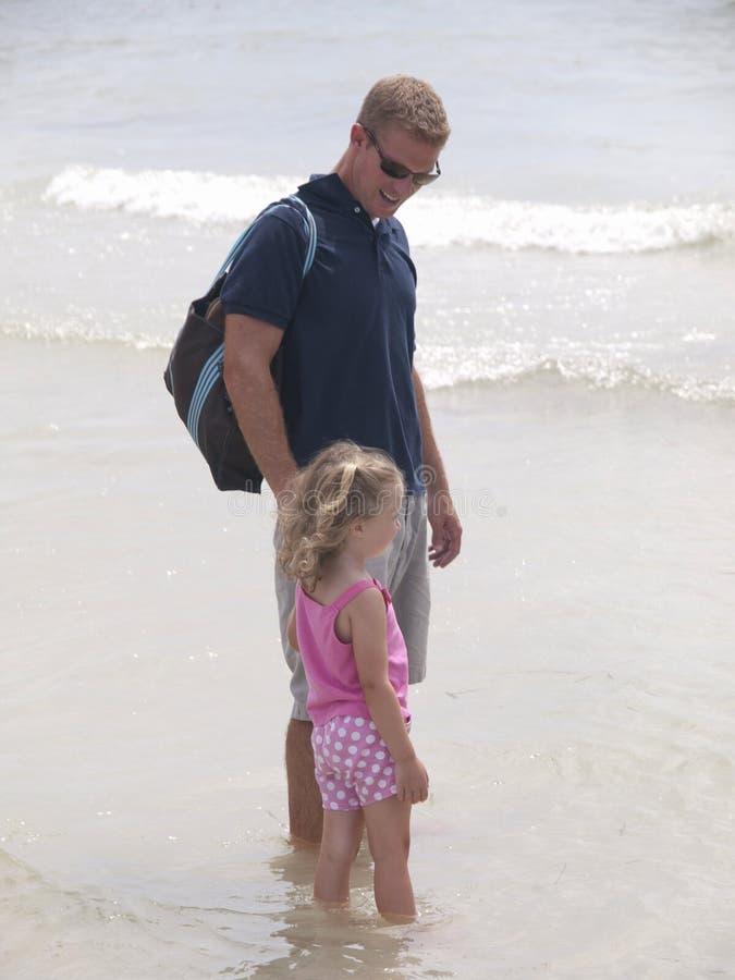 Vader en dochter die op het strand lopen royalty-vrije stock afbeelding