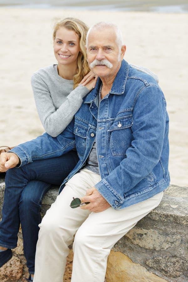 Vader en dochter die op muur door strand wordt gezeten royalty-vrije stock foto