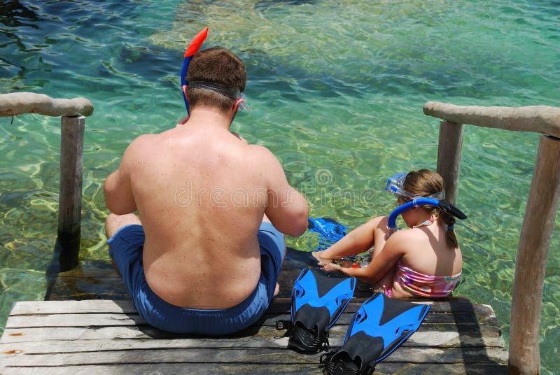 Vader en dochter die op vinnen en masker zetten stock afbeeldingen