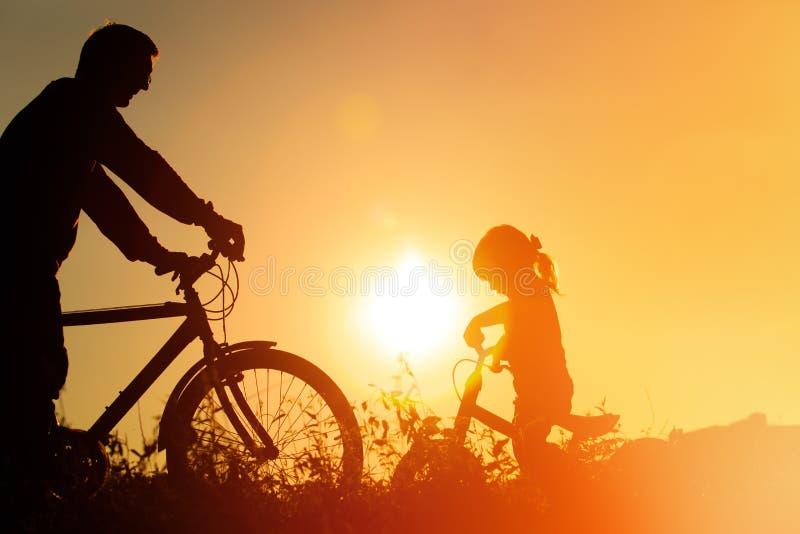 Vader en dochter die pret berijdende fiets bij zonsondergang, actieve familiesport hebben royalty-vrije stock foto's