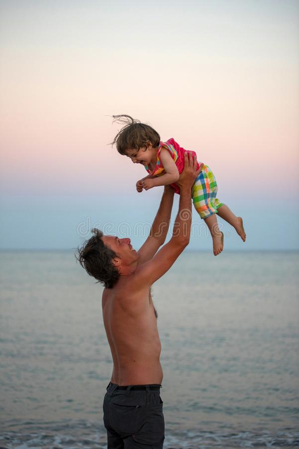 Vader en dochter die pret hebben bij strand stock afbeelding
