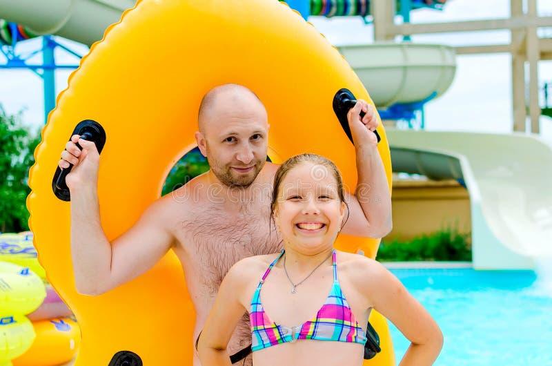 Vader en dochter die pret op waterdia's hebben in aquapark stock afbeeldingen