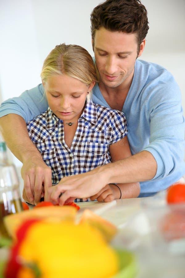 Vader en dochter die samen koken stock foto's