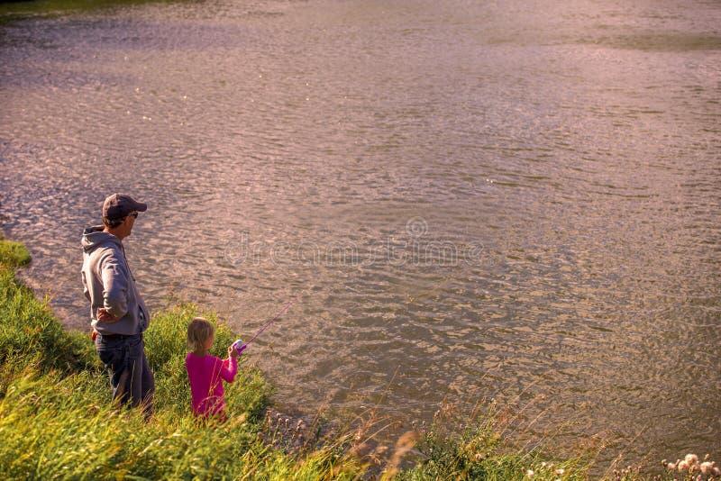 Vader en dochter die terwijl visserij ontspannen royalty-vrije stock fotografie