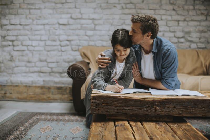 Vader en dochter die thuiswerk thuis doen stock afbeelding