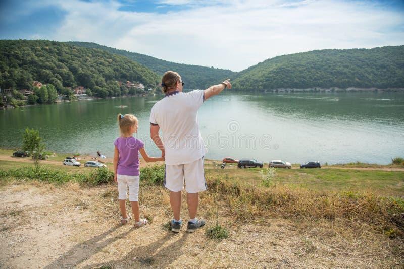 Vader en dochter die zich op de kust van het meer bevinden en handen houden De vader toont vooruit een hand aan bergen Bovanmeer, royalty-vrije stock afbeelding
