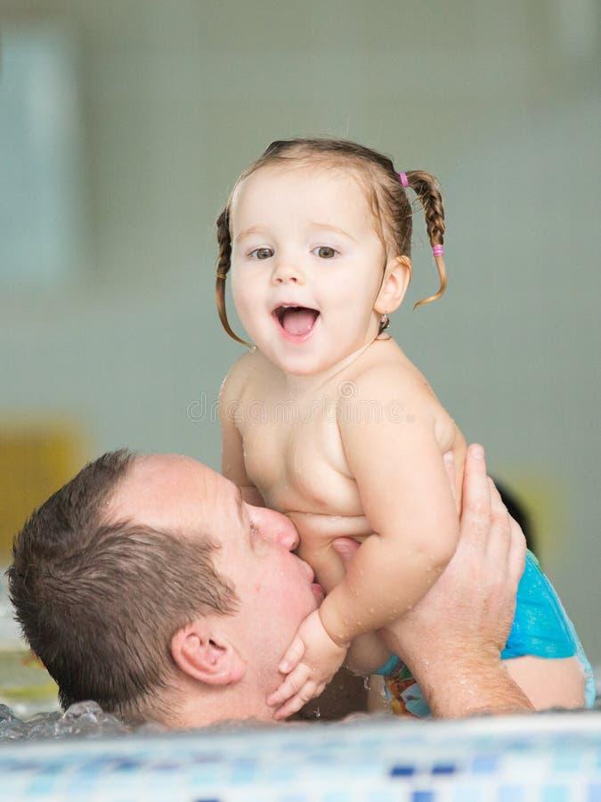 Vader en dochter in een pool stock afbeeldingen