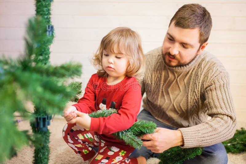 Vader en dochter het assembleren Kerstmisboom stock foto