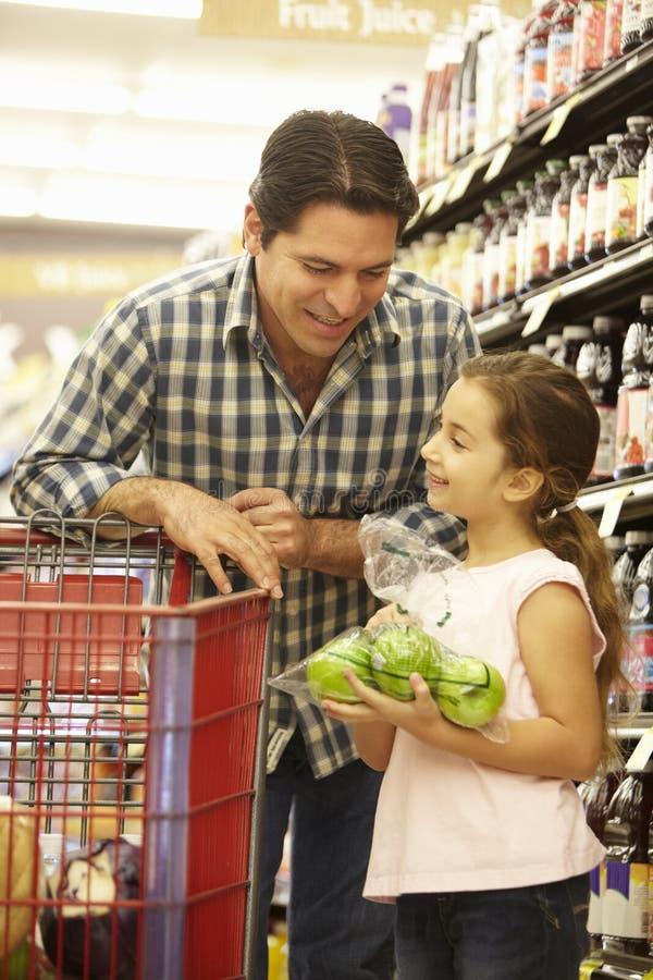 Vader en dochter het kopen fruit in supermarkt royalty-vrije stock foto's