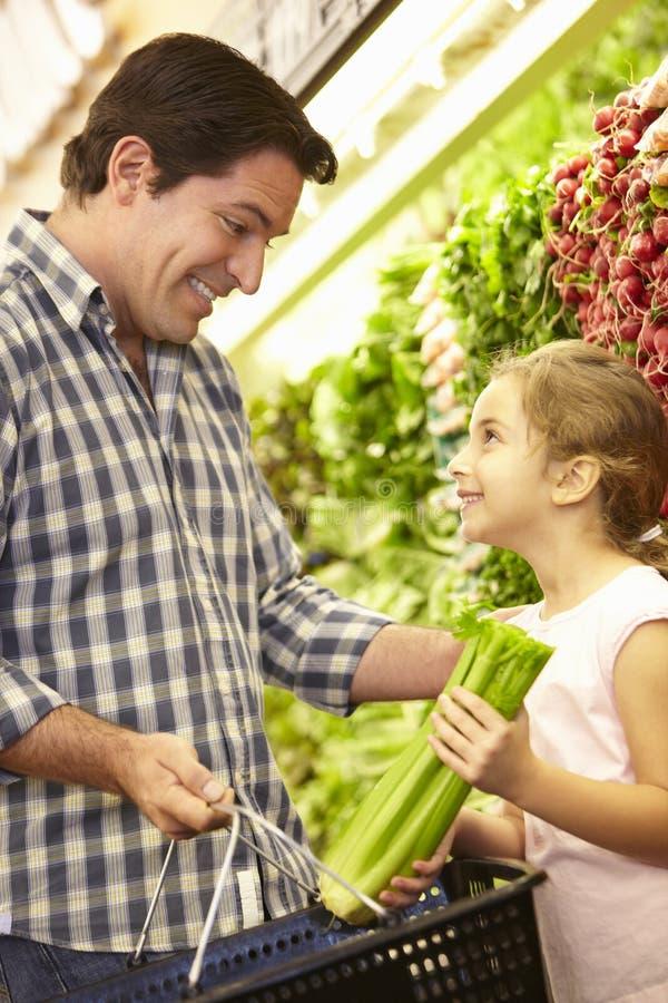 Vader en dochter het kopen groenten in supermarkt royalty-vrije stock fotografie