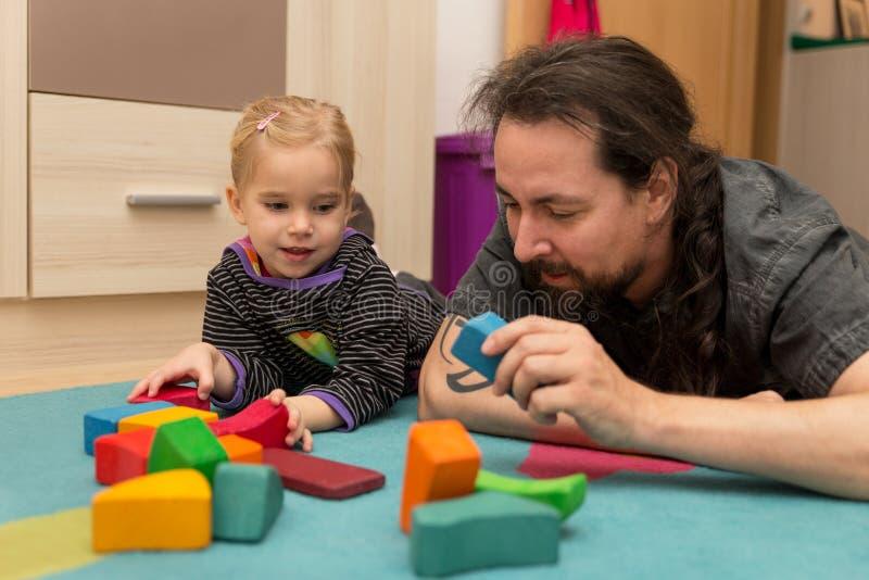 Vader en dochter het spelen met bakstenen stock foto's