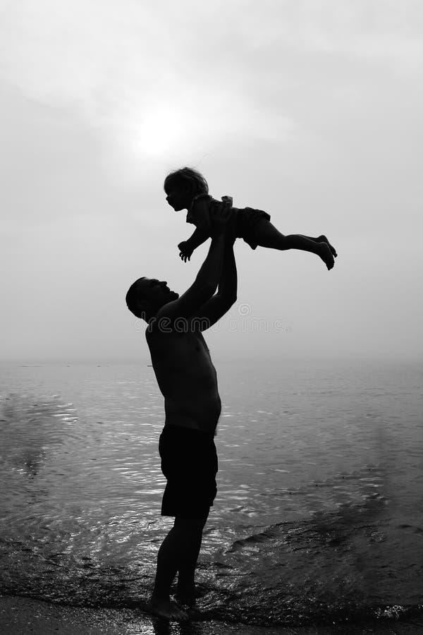 Vader en dochter het spelen op het strand bij zonsondergang royalty-vrije stock fotografie