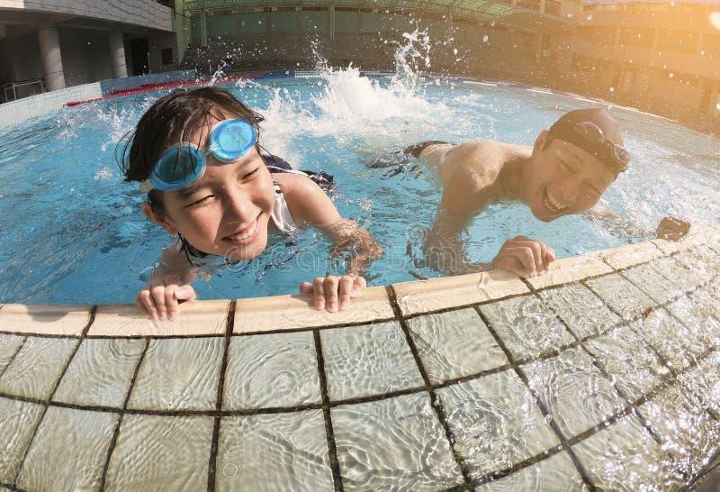 Vader en dochter het spelen in zwembad stock afbeeldingen