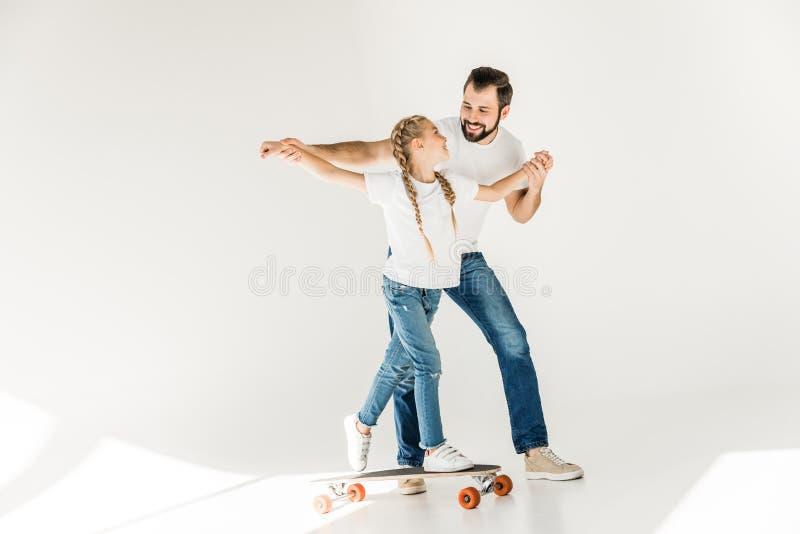 Vader en dochter met skateboard stock afbeelding