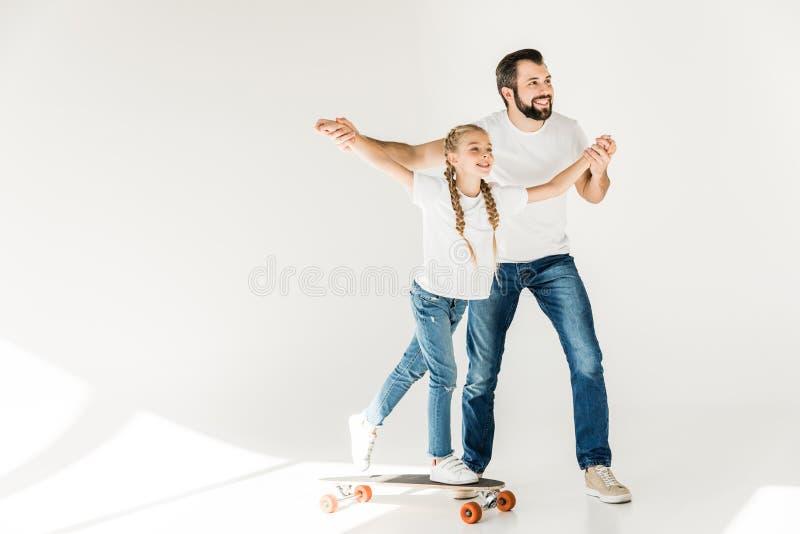 Vader en dochter met skateboard royalty-vrije stock afbeelding