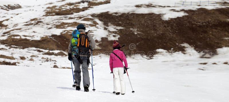 Vader en dochter met skistokken op sneeuwhelling in weinig sneeuwjaar stock afbeeldingen