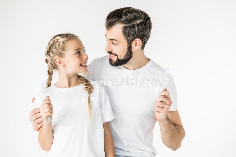 Vader en dochter met tandenborstels stock afbeeldingen