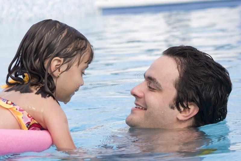 Vader en dochter in zwembad stock afbeeldingen