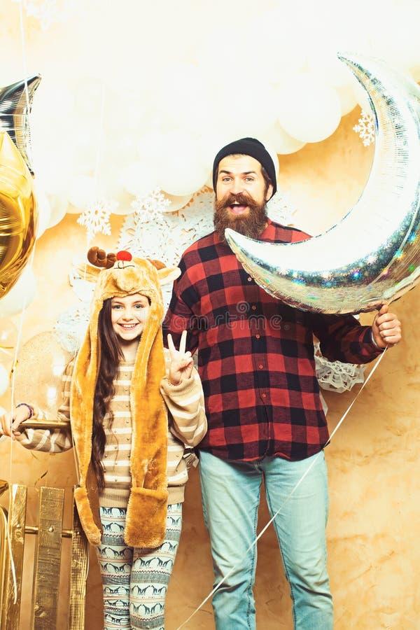 Vader en dochterglimlach met ballons bij Kerstmis Mens hipster en kind met de hand van het overwinningsteken De partij van de fam royalty-vrije stock afbeeldingen
