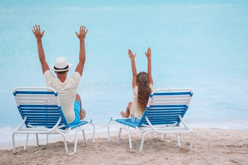 Vader en dochterhanden omhoog op strandzitting op chaise-longue stock afbeelding