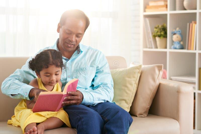 Vader en dochterlezing samen royalty-vrije stock afbeelding