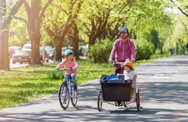 Vader en dochters die een rit met ladingsfiets hebben royalty-vrije stock foto's