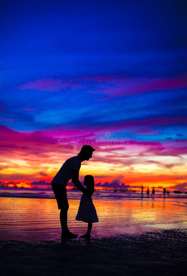 Vader en dochtersilhouetten in zonsondergang bij royalty-vrije stock foto's