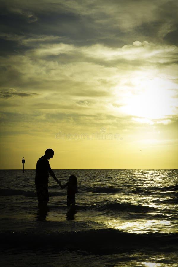 Vader en Dochterzonsondergangsilhouetten door het Overzees stock afbeeldingen
