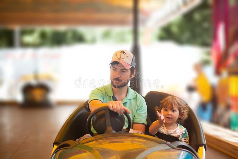 Vader en jong geitje die pret, themapark hebben royalty-vrije stock afbeelding