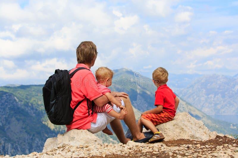 Vader en jonge geitjes die bergen op vakantie bekijken stock afbeeldingen