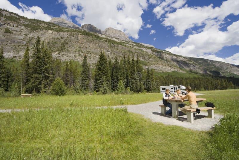 Vader en jonge geitjes die een picknick hebben royalty-vrije stock foto's