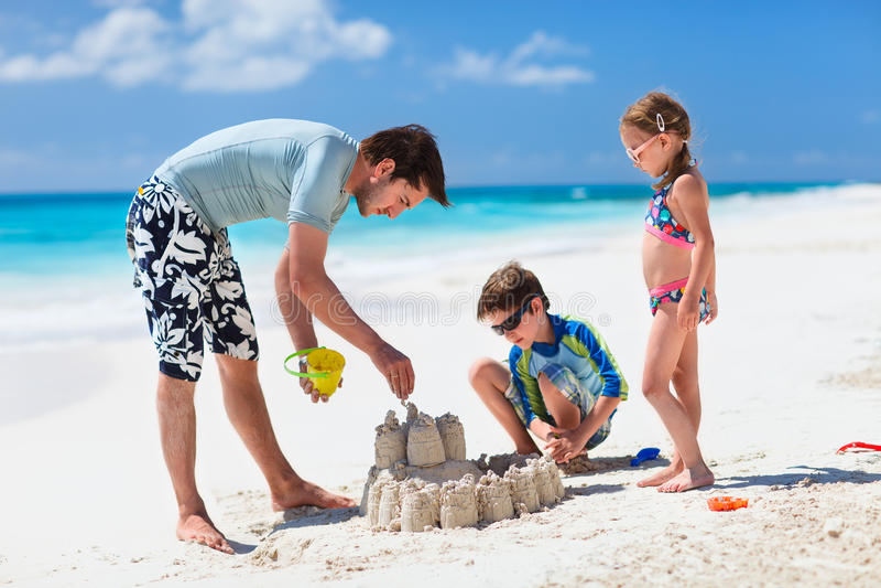 Vader en jonge geitjes die bij strand spelen stock afbeelding
