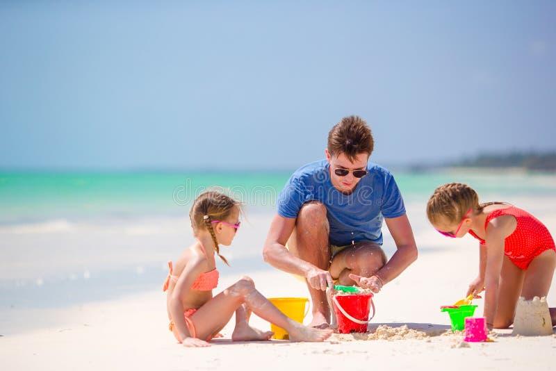 Vader en jonge geitjes die zandkasteel maken bij tropisch strand Familie het spelen met strandspeelgoed stock foto