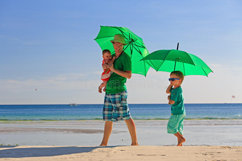 Vader en jonge geitjes met paraplu's op strandvakantie stock afbeelding