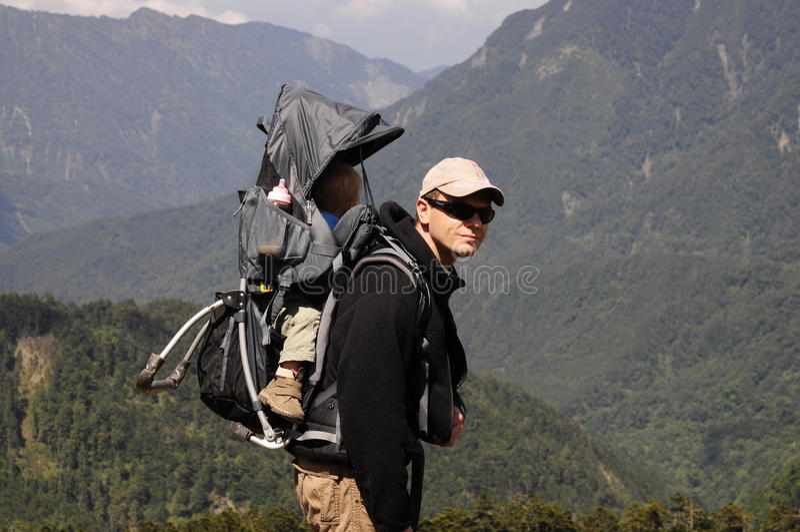 Vader en kind in de rugzak wandelingsberg stock afbeelding